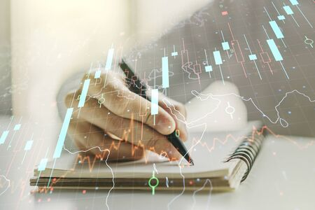 Multi exposure of abstract creative financial chart with world map and with man hand writing in notebook on background, research and analytics concept
