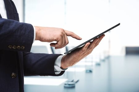 Man presses on the screen of a digital tablet in sunny boardroom, close up. Online technology concept