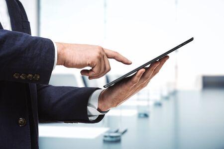 L'homme appuie sur l'écran d'une tablette numérique dans une salle de conférence ensoleillée, gros plan. Concept de technologie en ligne
