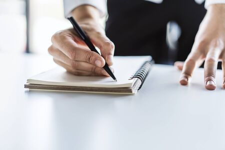 Man writes with a pen in notebook in a sunny office, business and education concept. Close up
