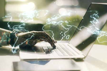 Abstract creative world map and hands typing on laptop on background, international trading concept. Multiexposure