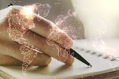Multi exposure of abstract creative digital world map and man hand writing in notebook on background, tourism and traveling concept Stock fotó