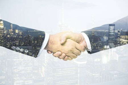 Multi exposure of handshake two businessmen on city skyline background, cooperation and coworking concept