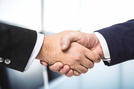 Handshake of two businessmen on the background of bright conference room, partnership concept, close up