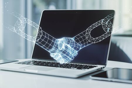 Double exposure of blockchain technology with handshake hologram on laptop background. Research and development decentralization software concept