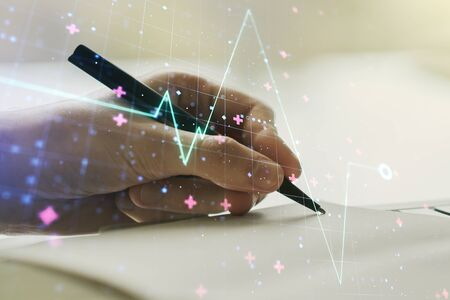Creative abstract heart pulse hologram and man hand writing in diary on background, online medical consulting concept. Multiexposure