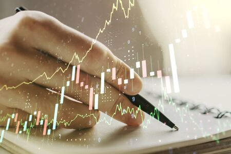 Multi exposure of abstract financial graph with hand writing in notebook on background, financial and trading concept