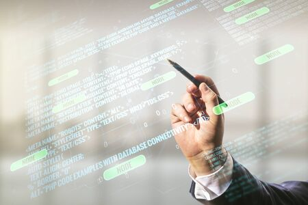 Double exposure of programmers hand with pen working with abstract creative programming illustration on blurred office background, big data and blockchain concept