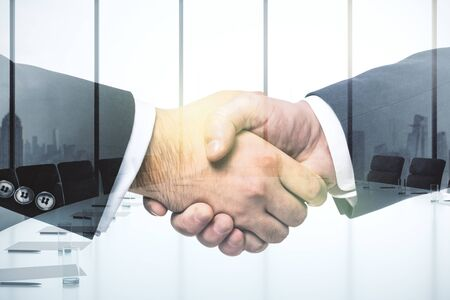 Handshake of two businessmen on conference room interior background, deal and partnership concept. Multiexposure