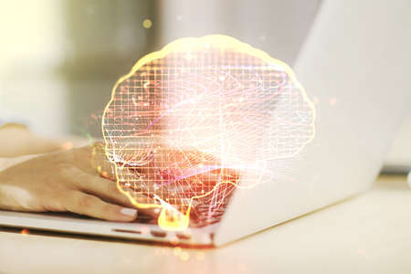 Creative artificial Intelligence concept with human brain hologram and hands typing on laptop on background. Multiexposure