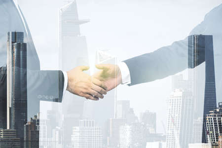 Multi exposure of handshake two businessmen on city skyline background, cooperation and coworking concept 免版税图像