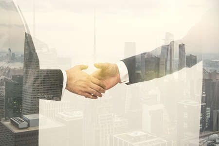 Multi exposure of handshake of two businessmen on city skyscrapers background, collaboration and teamwork concept