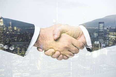 Multi exposure of handshake of two businessmen on city skyscrapers background, collaboration and teamwork concept Banque d'images