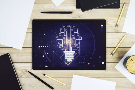 Modern digital tablet monitor with creative light bulb hologram and chip, idea and brainstorming concept. Top view. 3D Rendering