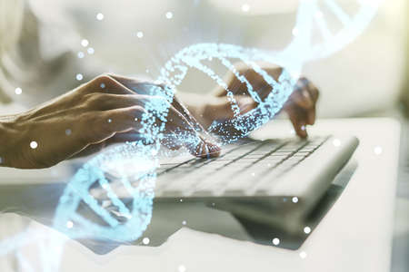 Double exposure of creative DNA hologram and hands typing on laptop on background. Bio Engineering and DNA Research concept