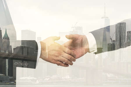 Handshake of two businessmen on modern city skyline background, deal and partnership concept. Multiexposure