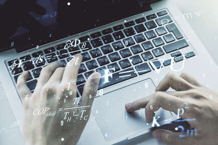 Double exposure of creative scientific formula concept with hands typing on laptop on background, research and development concept 免版税图像