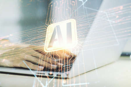Double exposure of creative artificial Intelligence icon with hands typing on laptop on background. Neural networks and machine learning concept