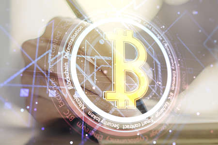 Creative Bitcoin concept with woman hand writing in diary on background. Double exposure Stock Photo