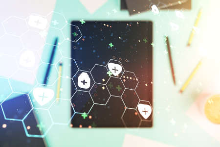 Double exposure of creative abstract medical hologram and digital tablet on background, top view. Healthcare technolody concept Stock Photo