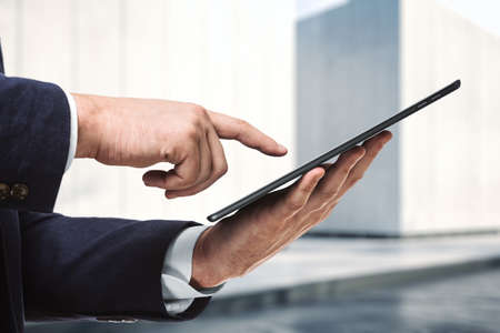 Businessman holds digital tablet and clicks on screen near the exterior of the business center on a sunny day, close up. Search concept