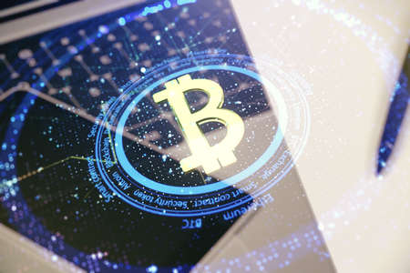 Double exposure of creative Bitcoin symbol with modern laptop on background. Cryptocurrency concept Stock Photo