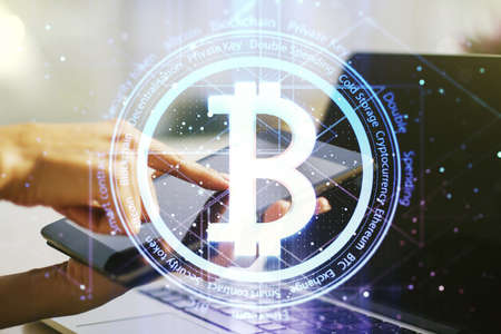 Double exposure of creative Bitcoin symbol hologram and hand working with a digital tablet on background. Mining and blockchain concept