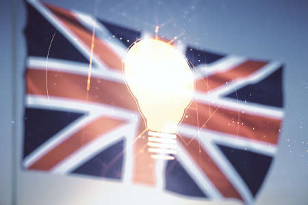 Abstract virtual light bulb illustration on British flag and sunset sky background, future technology concept. Multiexposure
