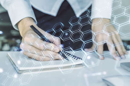 Creative concept of wireless technology with hexagon hologram and hand writing in notebook on background with laptop. Big data and database concept. Multiexposure