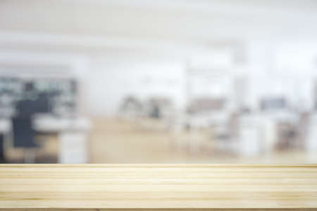 Empty table top made of wooden dies with sunny furnished office on background, template