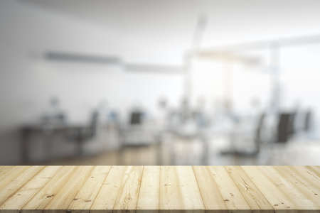 Blank wooden table top with light furnished office on background, mockup