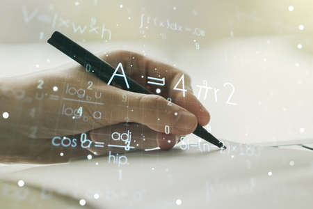 Creative scientific formula hologram with man hand writing in notepad on background, research concept. Multiexposure