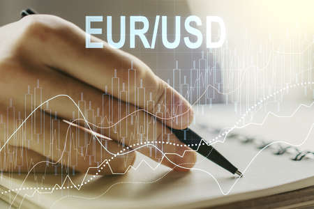 Creative EURO USD forex graph sketch and man hand writing in notepad on background, strategy and forecast concept. Multiexposure