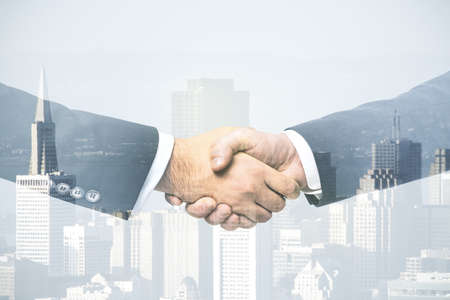Double exposure handshake of two businessmen on office buildings background, collaboration and cooperation concept