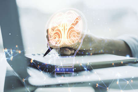 Creative light bulb with human brain hologram and hand writing in notepad on background with laptop, artificial Intelligence and neural networks concept. Multiexposure