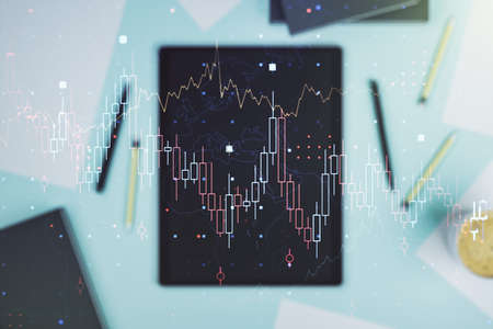 Abstract creative financial graph and modern digital tablet on desktop on background, top view, financial and trading concept. Multiexposure