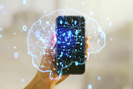 Double exposure of creative artificial Intelligence symbol and hand with cell phone on background. Neural networks and machine learning concept