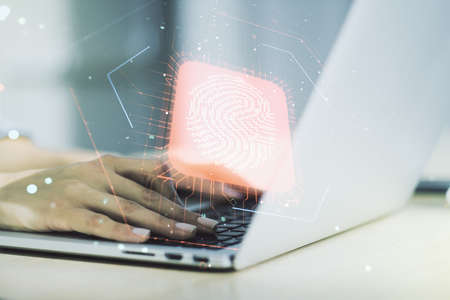 Double exposure of abstract creative fingerprint hologram with hands typing on laptop on background, protection of personal information concept