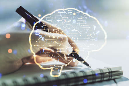 Creative artificial Intelligence concept with human brain hologram and woman hand writing in notebook on background. Multiexposure