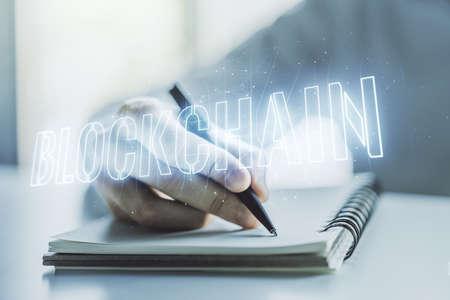 Creative abstract blockchain technology hologram and man hand writing in diary on background, cryptography and decentralization concept. Multi exposure