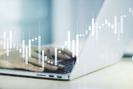Abstract creative financial graph with hand typing on laptop on background, forex and investment concept. Multiexposure