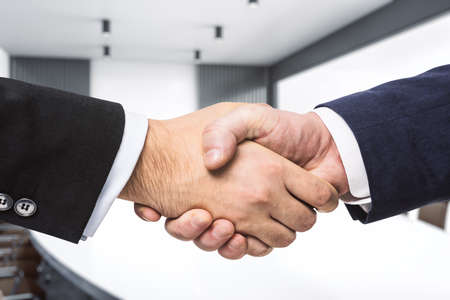 Handshake of two businessmen on the background of bright conference room, partnership concept, close up Banco de Imagens