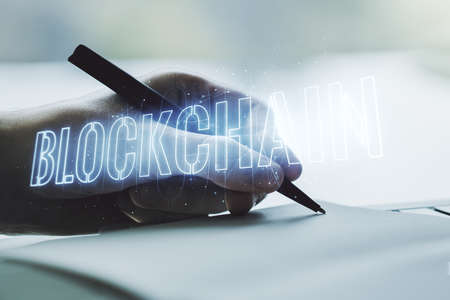 Creative concept of blockchain technology and man hand writing in notebook on background. digital money transfers and decentralization concept. Multiexposure