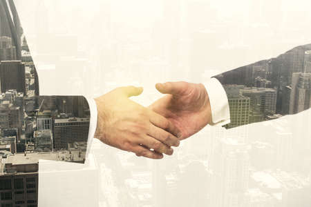 Double exposure of handshake two businessmen on modern skyscrapers background, research and strategy concept