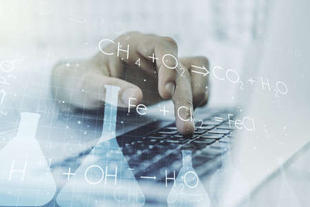Creative chemistry concept with hands typing on laptop on background. Multi exposure