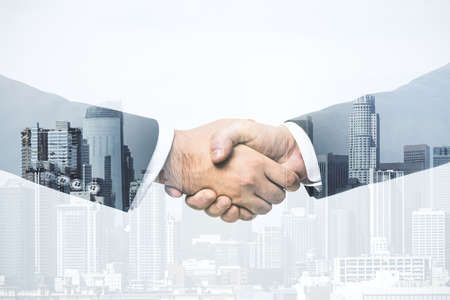 Handshake of two businessmen on modern cityscape background, deal and trading concept. Multiexposure