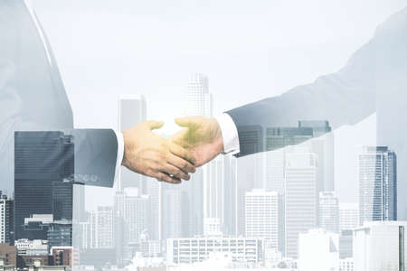 Double exposure of handshake two businessmen on modern skyscrapers background, research and strategy concept Zdjęcie Seryjne