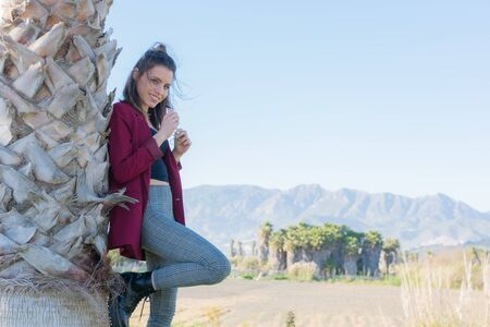 Young and friendly woman posing next to a palm tree with mountains and clear sky in the background