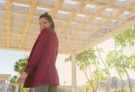 Young and cheerful woman in contrapicado view under a roof of concrete boxes open to the sky in a park Reklamní fotografie