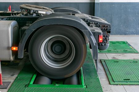 Truck wheel rotating on rollers to control the brakes and measure distances traveled by the tire for the vehicle's job registration device.